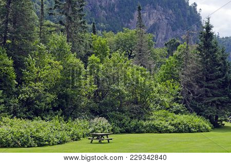 Barbecue Table On Green Grass Under Rocky Cliff.