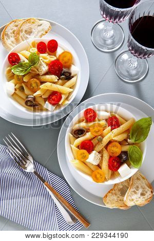 Healthy Summer Light Pasta Salad With Fresh Raw Tomatoes, Anchovies And Capers. Glasses Of Red Wine