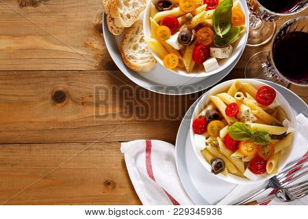 Healthy Summer Light Pasta Salad With Fresh Raw Tomatoes, Anchovies And Capers. Glasses Of Red Wine.