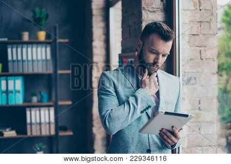 Stylish Ponder Brunet Bearded Broker Is Looking At The Screen Of Device, Holding His Tablet, Standin