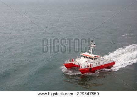 Modern Tugboat Of Red And White Color In The Sea Closeup.