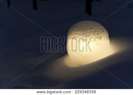 Glowing Round Matte Lantern In A Snowdrift, Reminiscent Of A Fallen Moon