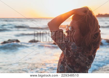 Young Woman Enjoying Sunset And Waves At The Beach