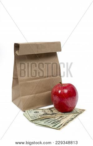Vertical Shot Of The Front Of A Brown Paper Bag With The Top Folded Down With A Red Shiny Apple Sitt