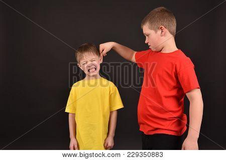 Bad Behavior. Children. Two Boys On A Black Background.