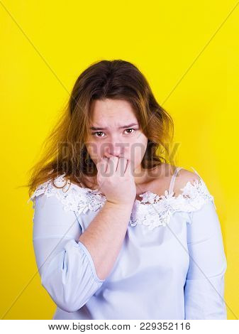 Closeup Portrait Of Stressed Young Woman Biting Her Nails, Looking With Alarm, Isolated Yellow Backg
