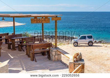 Zakynthos, Greece - October 1, 2017: Snack Bar With View Of Blue Sea Water On Porto Roxa Beach. Zaky