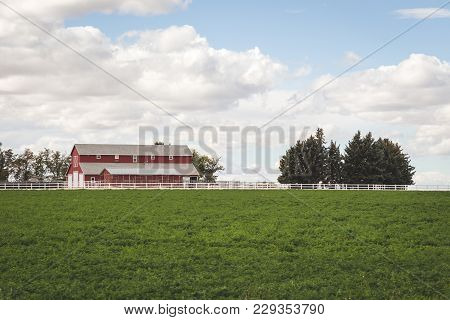 Red Farm House And Trees Under Cloudy Blue Sky. Green Field In Foreground.
