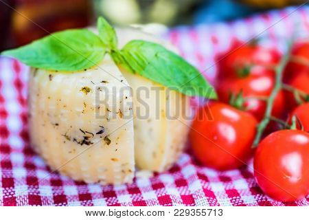 Close Up Rustic Cheesehead With Herbs And Tomatoes On Checkered Tablecloth, Selective Focus