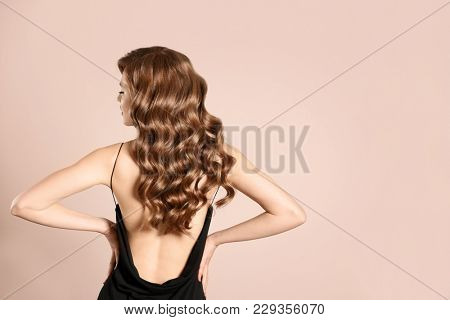 Beautiful young woman with long wavy hair on light background