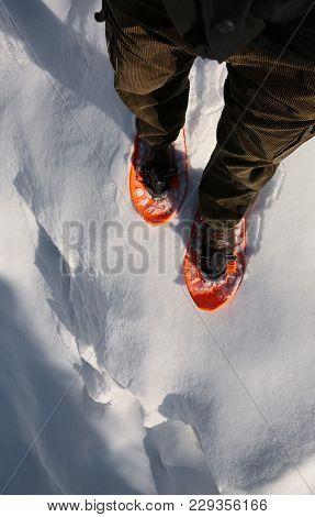 Man With Orange Snowshoes Walks Near A Deep Crevasse
