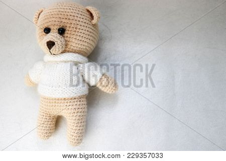 A Knitted Homemade Beautiful Cute Little Bear In A White Sweater With Black Eyes, A Soft Toy Tied Wi