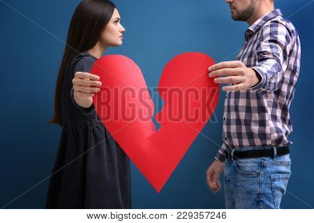 Young couple tearing paper heart in half on color background. Relationship problems