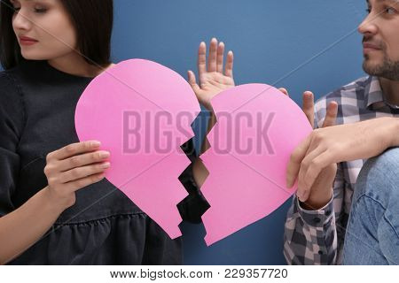 Young couple fighting while holding paper heart cut in half on color background. Relationship problems