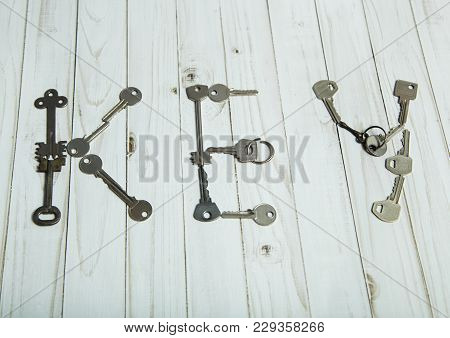 The Word Key Is Laid Out On A White Surface Of Old Steel Keys.