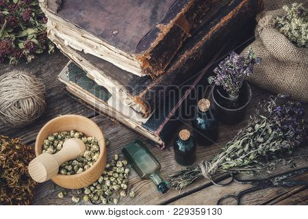 Tincture Bottles, Assortment Of Dry Healthy Herbs, Old Books, Mortar, Scissors On Old Wooden Desk. H