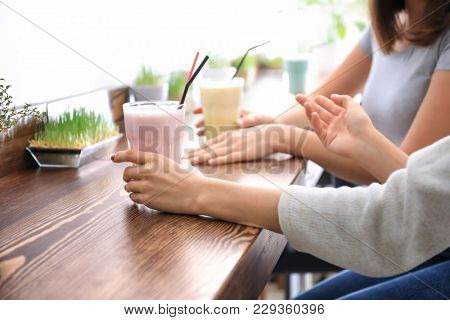 Young women with protein shakes in sport bar