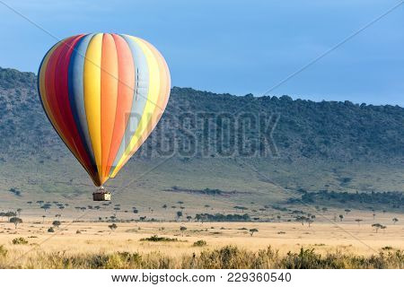 Low flying colourful balloon over the grasslands of the Masai Mara. No recognizable people visible.