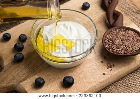 Flax Seed Oil Is Being Poured Over Cottage Cheese In A Bowl, With Flax Seeds And Blueberries In The