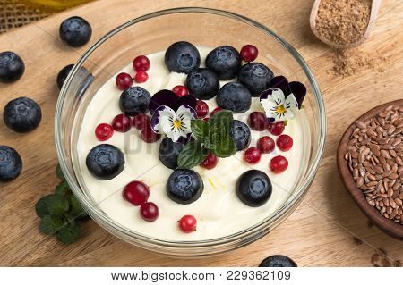Closeup Of Cottage Cheese Blended With Flax Seed Oil, Topped With Fresh Blueberries, Frozen Wild Cra