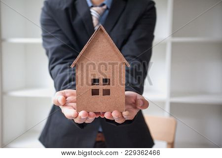 Real Estate Agent With House Model. Real Estate Broker Concept
