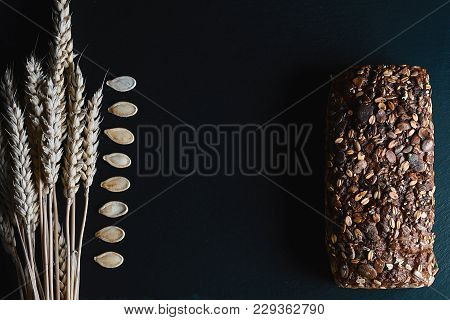 Dark Rye, Cereal Bread With Sunflower Seeds, Whole Bread, Wheat Stems, Pumpkin Seeds On A Dark Backg