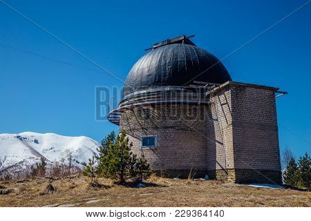 Astronomical Observatory With Telescope Against The Background Of The Blue Sky And Snowy Peaks Of Th