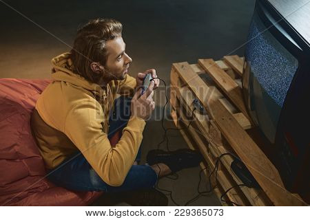 Top View Interested Bearded Male Typing In Joystick While Looking At Display Of Retro Television Set