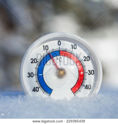 Thermometer with celsius scale placed in a fresh snow showing sub-zero temperature minus 9 degree - cold winter weather concept