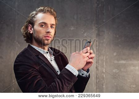 Portrait Of Earnest Man Sending Message In Cellphone While Looking At Camera. Electronic Equipment C
