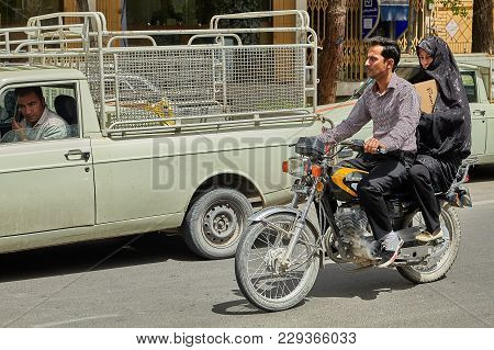 Couple Is Riding A Motorbike On Busy Street, Kashan, Iran.