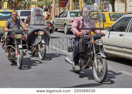 Kashan, Iran - April 27, 2017: Motorcyclists Riding On Motorcycles On The Roadway A City Street.