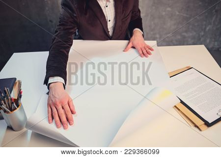 Close Up Male Hands Holding Blueprint. He Locating At Table In Office. Job With Paper Concept. Top V