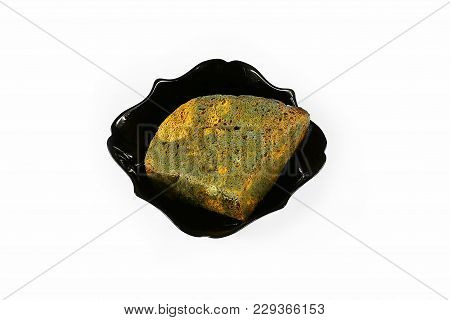 Half A Loaf Of Mouldy Rye Bread In A Black Plate Isolated On White Background, Concept Of Inedible P