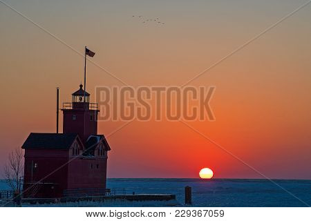 Michigan Red Lighthouse On Lake Michigan Pier In Winter At Sunset Time