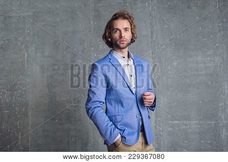 Portrait Of Pensive Unshaven Young Businessman Having Dream While Putting Hand In Pocket
