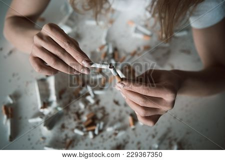 Top View Close Up Of Female Hands Breaking Ciggy, Shredded Cigarettes Are Lying On Table. Focus On C