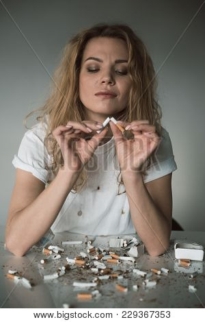 Portrait Of Pleased Attractive Female Looking At Cigarette While Breaking It. Isolated On Background