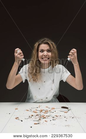 Waist Up Portrait Of Young Woman Sitting At Table And Squeezing Cigarette Packs In Hands Expressing