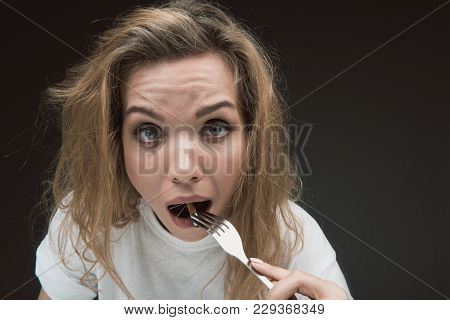 Portrait Of Woman With Shocked Facial Expression Putting Into The Mouth Prickly Tobacco Product. Cop