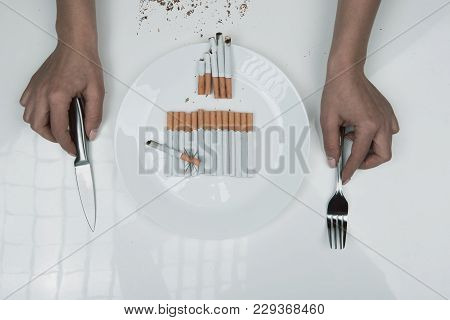 Top View Of Female Hands Taking Cutlery From The Table With Plate Full Of Cigarettes