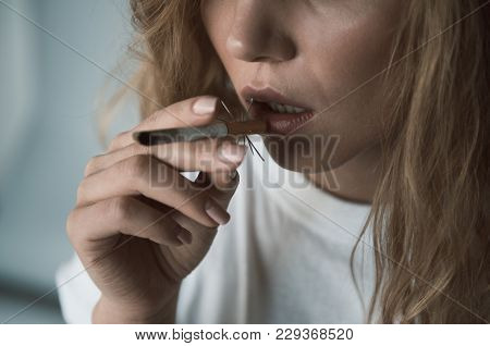 Close Up Of Female Hand Holding Ciggy Punctured With Needles Near Her Lips. Isolated On Background