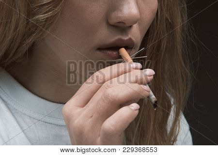 Injury Concept. Close Up Of Female Hand Bringing To Mouth Prickly Ciggy. Isolated On Background