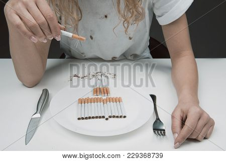 Woman Sitting In Front Of Plate With Nicotine With Barbed Cigarette In Hand. Close Up