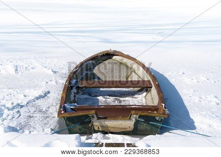 Old Rowing Boat In The Frozen Lake On A Sunny Winter Day, Concept Metaphor For Burn Out, Slow Down A