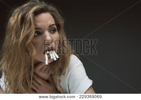 Portrait Of Pensive Girl Holding Few Rollups With Teeth And Looking Aside. Copy Space In Right Side.