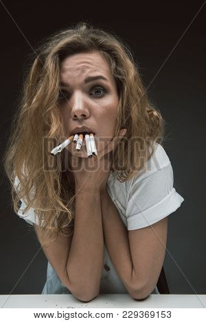 Portrait Of Discontent Girl Disliking Smoking. She Is Gulping Rollups And Holding Arms On Neck. Isol