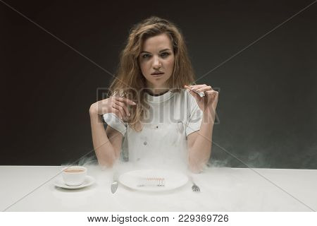 Portrait Of Calm Woman Resting At The Table And Puffing Coffin Nail. Smoke Falling On The Desk. Copy