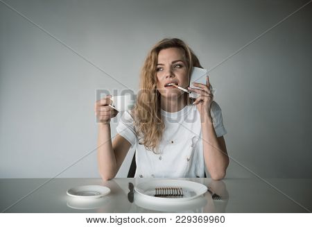 Portrait Of Thoughtful Woman Puffing While Relaxing And Communicating By Cellphone. Plate Full Of Ci
