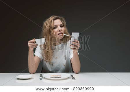 Portrait Of Confident Female Sitting And Fuming. She Is Holding Beverage And Gadget In Hands. Copy S